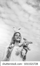 happy easter girl in pink bunny ears with yellow painted egg and rabbit toy, has long blonde hair and smiling adorable face outdoor on blue cloudy sky background. traditional spring holiday food