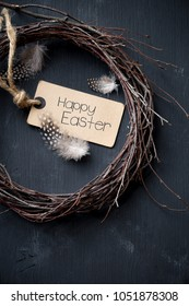 Happy Easter greeting card. Rustic handmade wreath witih antag and quail feathers for Easter concept