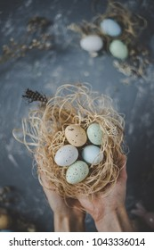 Happy easter. Hands holding easter eggs in nest with easter decoration, top view.
