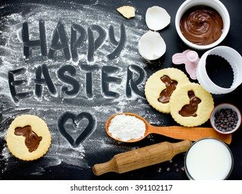 Happy Easter holiday food baking background cookies bunny with ingredients on black flour background top view