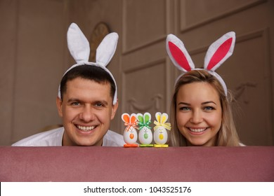 Happy Easter. Joyful couple with bunny ears smiling near rabbit toys at Easter day. Funny young family or friends at Easter sunday