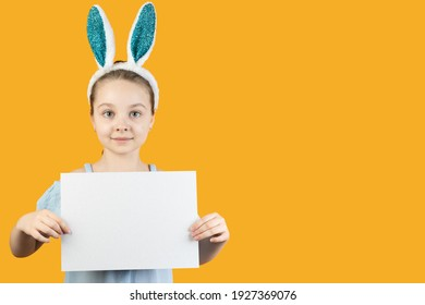 Happy Easter, kids. A girl in rabbit ears on her head holds a blank sheet of cardboard in her hands. Baner, copy space.