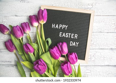 Happy Easter lettering on small chalkboard surrounded by pink wooden Easter bunny and white flowers. Greeting card, ad, promotion, poster, flyer, web-banner, article.