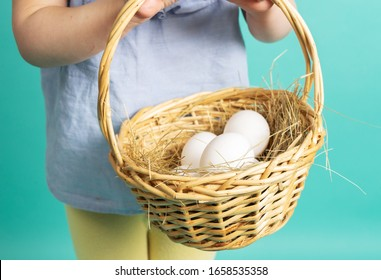 Happy Easter: a little girl holding a basket of eggs in her hands.