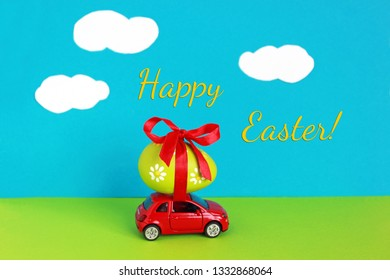 Happy Easter!, little red toy car with a colored easter egg tied on its roof driving through a green landscape with blue sky and clouds