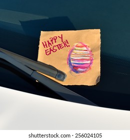 Happy Easter - Message under a windshield wiper with hand written text and a hand drawn easter egg