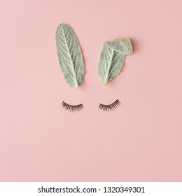 Happy Easter minimal concept. Bunny rabbit face made of natural green leaves with eyelashes on pastel pink background. Flat lay.