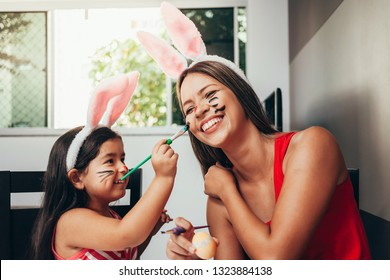 Happy easter! A mother and her daughter painting Easter eggs. Happy family preparing for Easter. Cute little child girl wearing bunny ears on Easter day