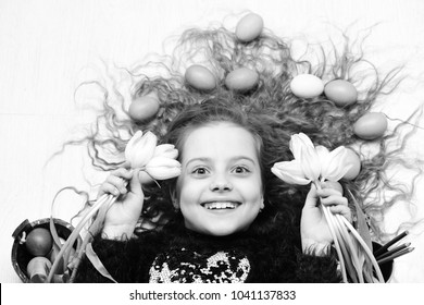 happy easter, mothers or womens day spring holiday, small child, girl with colorful eggs in long curly hair, has smiling face laying isolated on white background, childhood and happiness