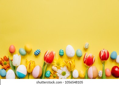 Happy Easter nest of candy, bird and polka dot eggs with yellow tulips and robin on white wood table background.
