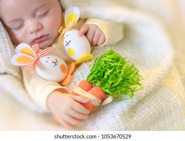 Happy easter, portrait of a cute little baby sleeping at home with his toys, decorated Easter eggs rabbits, calm pretty child napping