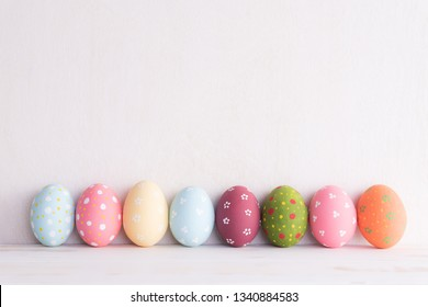 Happy easter! Row Easter eggs on bright white wooden background.