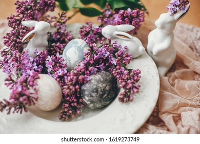 Happy Easter. Rustic composition of natural dyed easter eggs, lilac flowers and bunny rabbits on linen fabric on wooden table. White ceramic bunny and spring flowers.