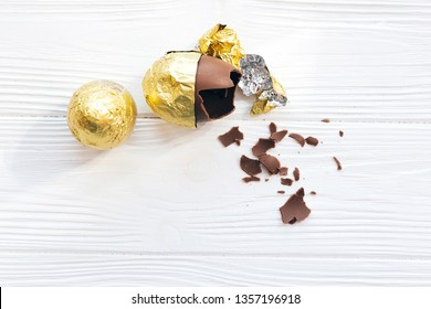 Happy Easter. Stylish Easter egg in golden foil and broken chocolate egg with chocolate pieces on white wooden background, space for text. Modern gold easter eggs. Holiday gift