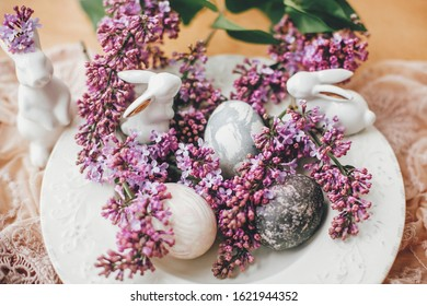 Happy Easter. Stylish Easter eggs on vintage plate, white bunnies and lilac flowers on fabric on wooden table. Rural composition of colorful natural dyed easter eggs and spring flowers