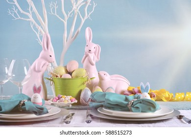 Happy Easter table setting with bunny and eggs centerpiece in pastel Spring color theme, with copy space, with faded lens flare filter.