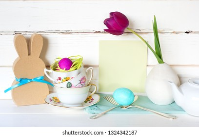 Happy Easter Tea Party or Meal Invite Card with Tea Cups, Bunny, Flower, Egg and Silverware in Modern Whimsical Arrangement with Shiplap Board Background.  Wide Horizontal with side view