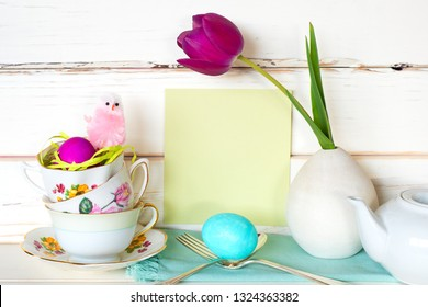 Happy Easter Tea Party or Meal Invite Card with Tea Cups, Pink Chick, Flower, Egg and Silverware in Modern Whimsical Arrangement with Shiplap Board Background.  Wide Horizontal with side view