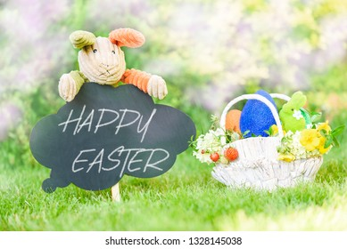 Happy Easter text on blackboard and basket with Eastertide symbols