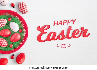 Happy easter text on white surface with eggs, basket and ladybug decorations beside.
