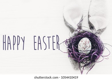 Happy Easter text. season's greetings card. bunny ears and stylish egg in nest on white wooden background flat lay. happy easter concept