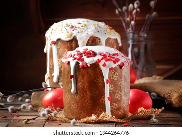 Happy Easter! Traditional Russian easter cake Kulich with colored red eggs, decorated with hearts, with twigs of fluffy willow. Vintage wooden table background, rustic style. Selective focus
