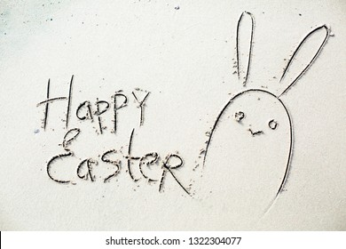 """""""Happy easter"""" written in the sand on sea background"""