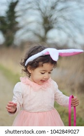 Happy Easter's day. A cute little girl wearing bunny ears and holding basket. Egg hunting.