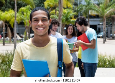 Happy egyptian scholarship student with group of international students outdoor on campus of university