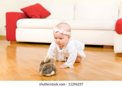 Happy eight month old baby girl crawling to rabbit toy on a hardwood floor in a living room