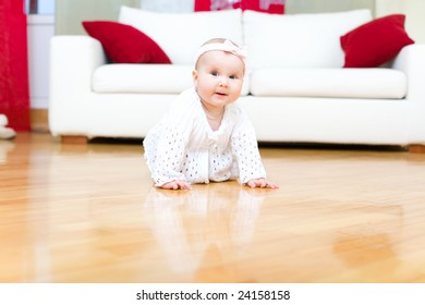 Happy eight month old baby girl crawling on a hardwood floor in living room