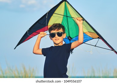 Happy eight year old boy in sunny glasses launches a bright kite at the seashore against a blue sky close up at sunset