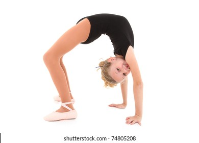 Happy eight year old caucasian girl in ballerina uniform doing bridge up, back bend over white with clipping path.