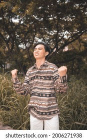A happy and elated teenager in a boho outfit pumps his fists after getting good grades or entering a new relationship. Outdoor park scene.