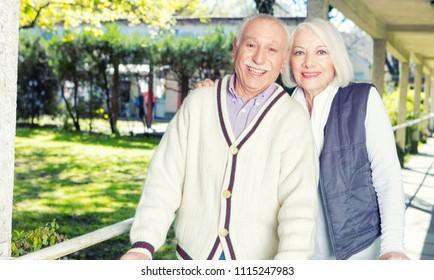 Happy elder couple in 70s relaxing together outdoor.