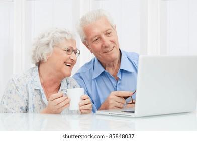 Happy elder couple enjoy together at laptop computer