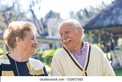 Happy elder couple smiling enjoying life in the garden.