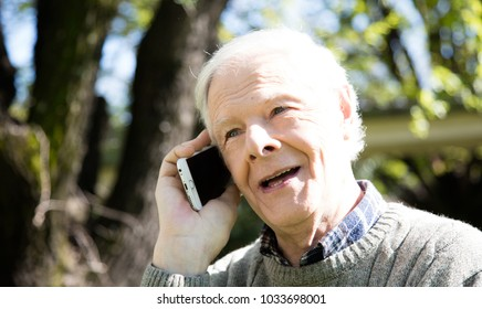 Happy elder man speaking to friend at the phone outdoor smiling.