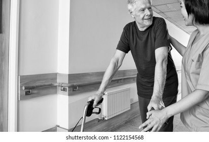 Happy elder man with walker talking to nurse in hospital corridor.