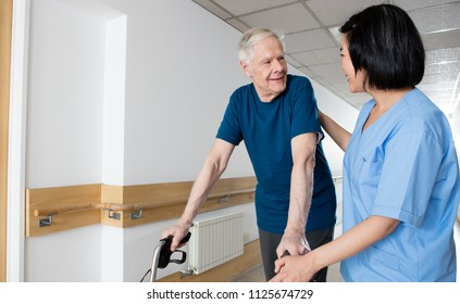 Happy elder man with walker talking to nurse in hospital corridor.