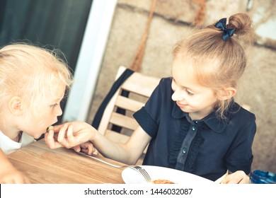 Happy elder sister feeding small sister in cafe restaurant concept children care childhood lifestyle
