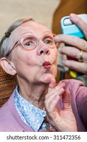 Happy elder woman taking duck face selfie