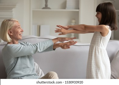 Happy elder woman teaching little adorable granddaughter doing exercises. Side view smiling small cute girl repeating hands moves for grandmother or middle aged nanny sitting on comfortable couch.