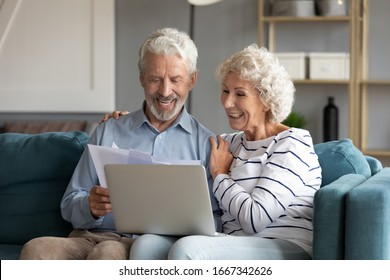 Happy elderly 60s couple sit rest on couch at home pay household expenses online on computer, smiling mature 50s husband and wife clients hold documents make payment on internet banking service