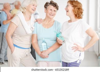 Happy elderly active girlfriends gossiping in a gym