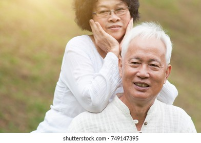 Happy elderly Asian old couple at outdoor park.