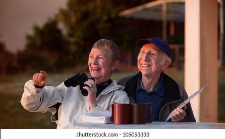 Happy elderly bird watchers outside in jackets