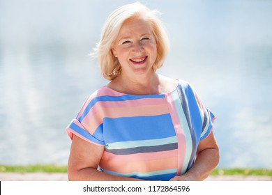 Happy elderly blonde woman in blue dress on the background of summer park
