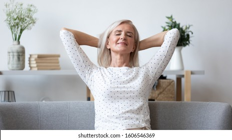 Happy elderly caucasian woman sit relax on couch hands over head taking day nap at home, smiling calm middle-aged female pensioner rest on cozy sofa in living room dream visualize or breathe fresh air