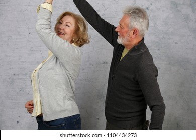 Happy elderly couple dancing and laughing